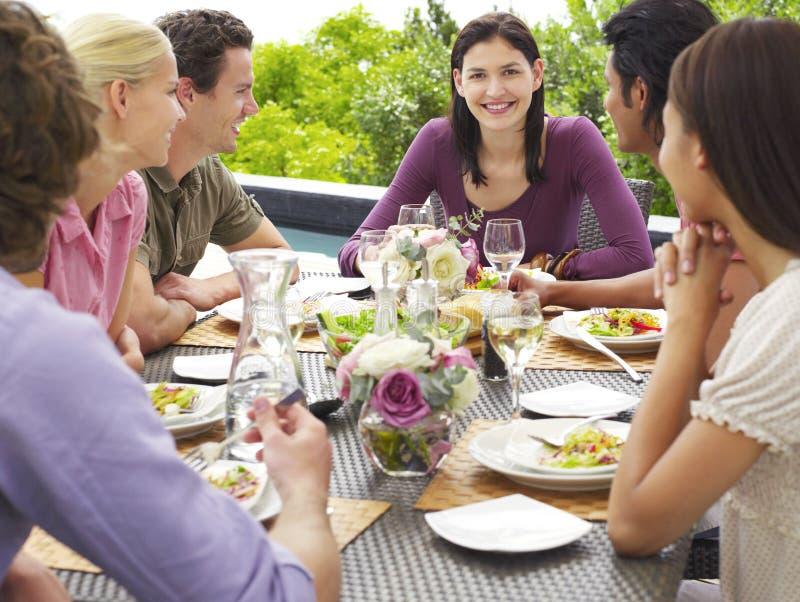 Mulher com os amigos que apreciam a refeição fora foto de stock