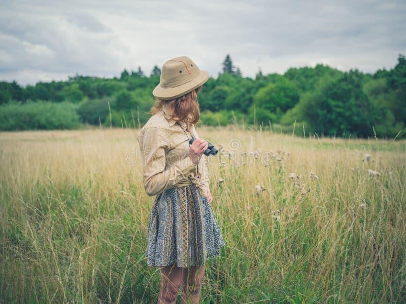 Mulher com os binóculos que estão no prado imagens de stock royalty free