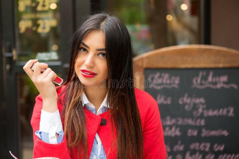 Mulher com os bordos vermelhos que mostram o batom, fora fundo da cafetaria fotografia de stock
