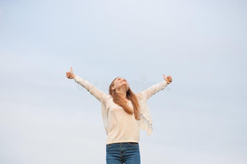 Mulher com os braços abertos no fundo do céu na manhã foto de stock