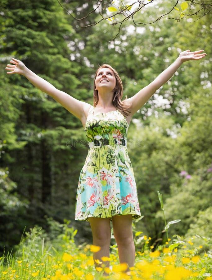 Mulher com os braços estendido no campo contra árvores fotos de stock