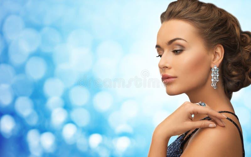 Mulher com os brincos bonitos do diamante sobre o azul imagens de stock royalty free