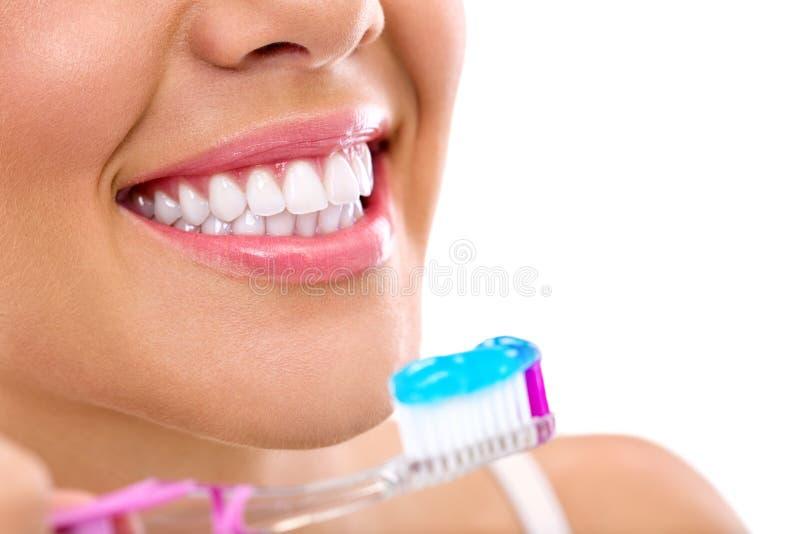 Mulher com os dentes saudáveis que guardam uma escova de dentes foto de stock royalty free