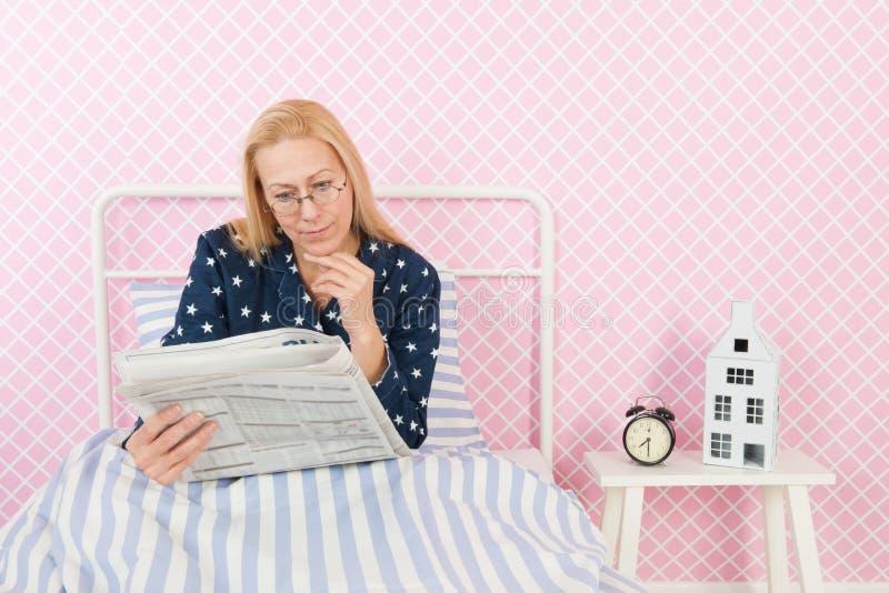 Mulher com os jornais na cama imagens de stock royalty free