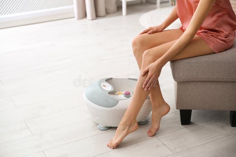 Mulher com os pés bonitos que sentam-se perto do banho do pé em casa, close up com espaço para o texto imagens de stock