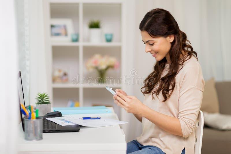 Mulher com os papéis e o smartphone que trabalham em casa imagens de stock
