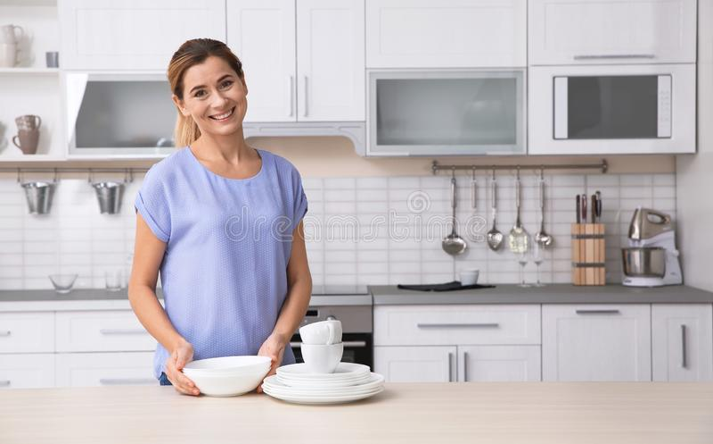 Mulher com os pratos limpos perto da tabela na cozinha fotos de stock