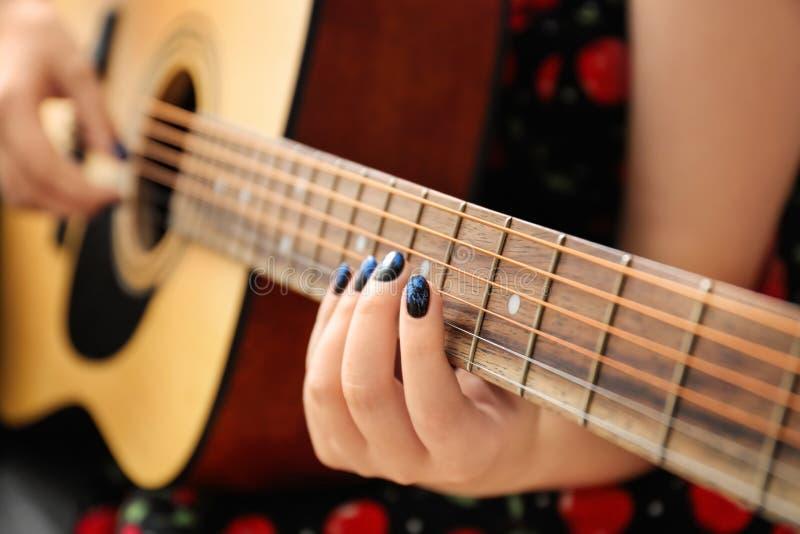 Mulher com os pregos à moda da cor que jogam a guitarra, close up fotografia de stock royalty free