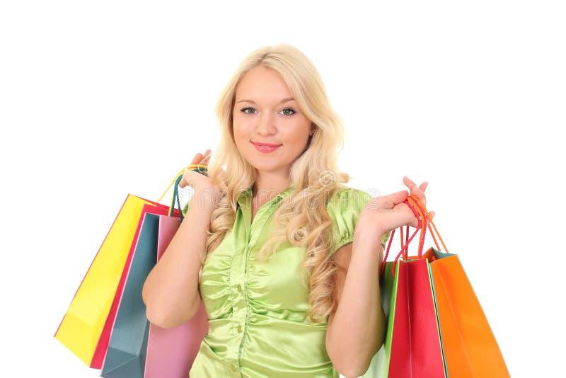 Mulher com os sacos de compra sobre o fundo branco imagem de stock