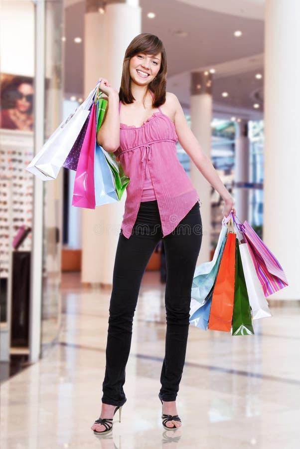 Mulher com os sacos de compras na loja fotografia de stock