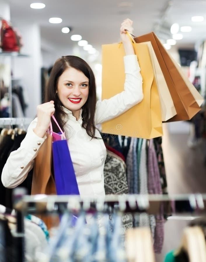 Mulher com os sacos de compras na loja imagens de stock royalty free