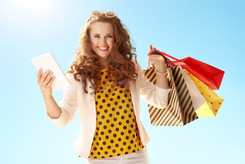 Mulher com os sacos de compras com o PC da tabuleta contra o céu azul fotografia de stock royalty free
