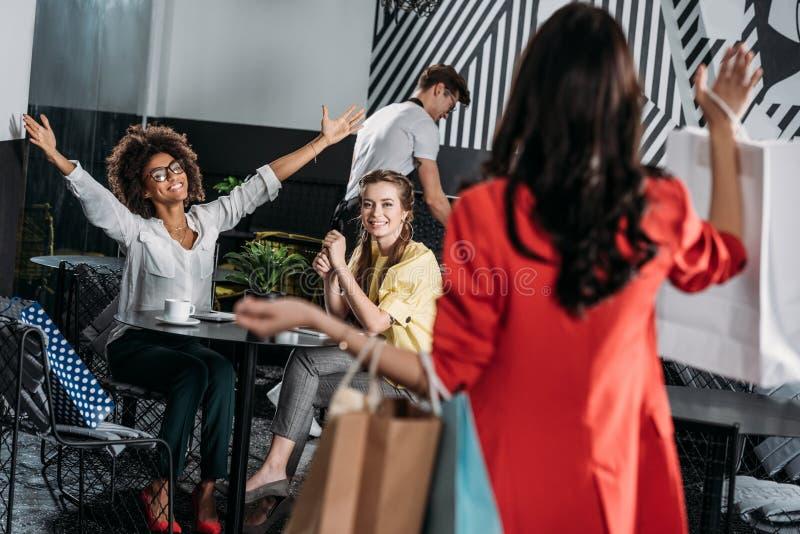 mulher com os sacos de compras que vão a seus amigos imagem de stock