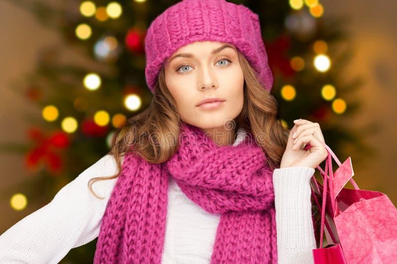 Mulher com os sacos de compras sobre luzes de Natal fotografia de stock