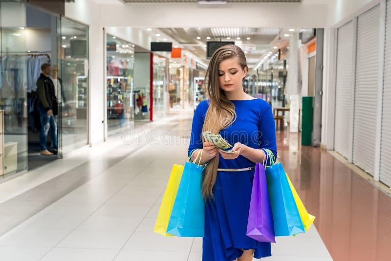 Mulher com os sacos que contam d?lares para comprar foto de stock