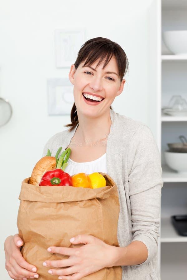 Mulher com os sacos shoping na cozinha imagens de stock royalty free