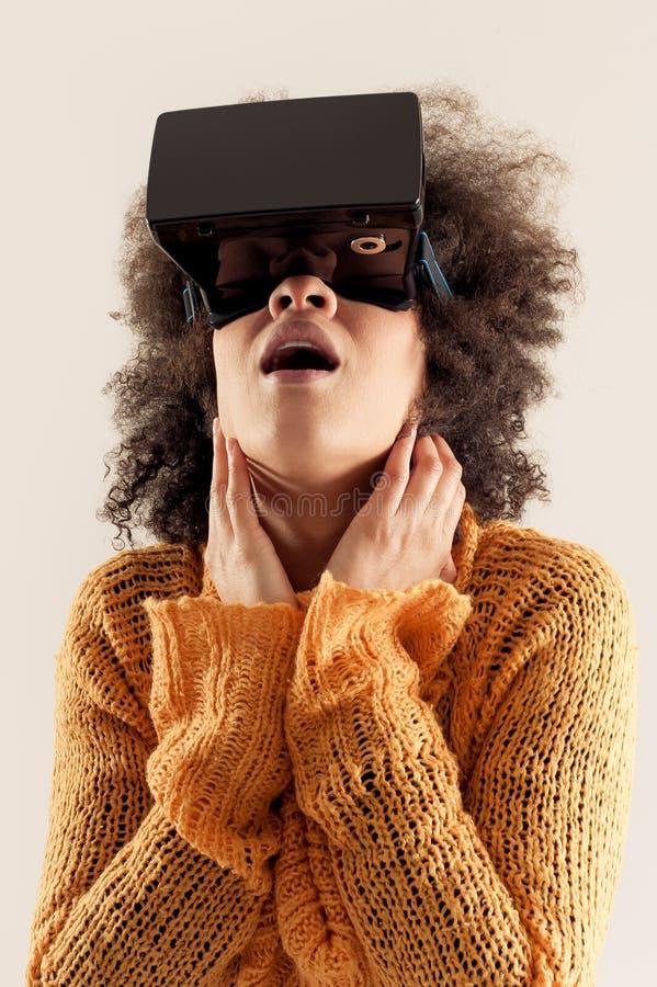 Mulher com os vidros da realidade virtual que jogam o jogo imagem de stock