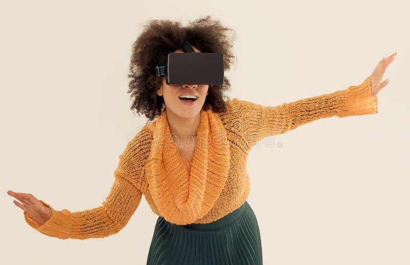 Mulher com os vidros da realidade virtual que jogam o jogo imagens de stock