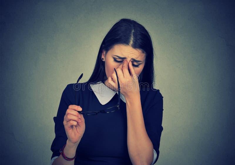 A mulher com os vidros que friccionam seus olhos sente cansado fotos de stock
