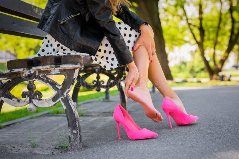 Mulher com pé ferido devido às sapatas incômodas imagens de stock