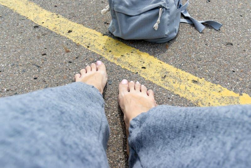 Mulher com pés desencapados e trouxa que senta-se em uma estrada asfaltada com uma única linha amarela veículo de espera da estra foto de stock