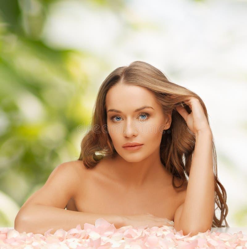 Mulher com pétalas cor-de-rosa e cabelo longo imagens de stock