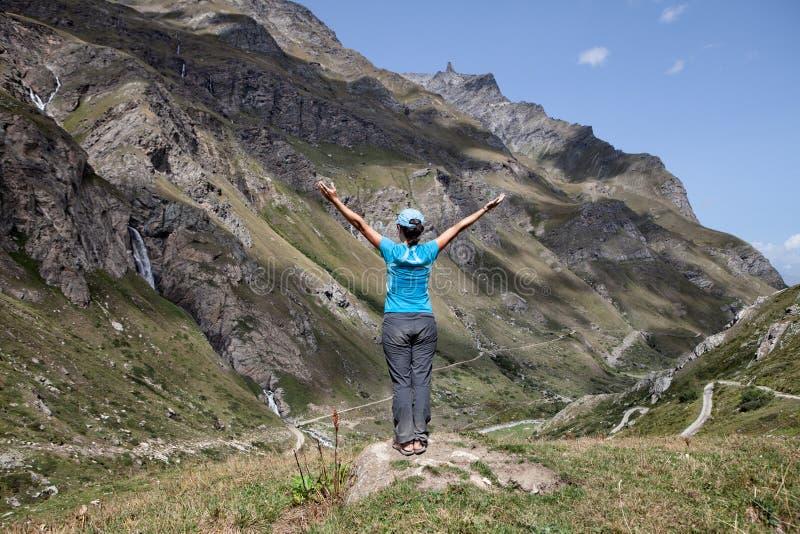 A mulher com partes traseiras abre os braços em uma paisagem montanhosa imagem de stock royalty free