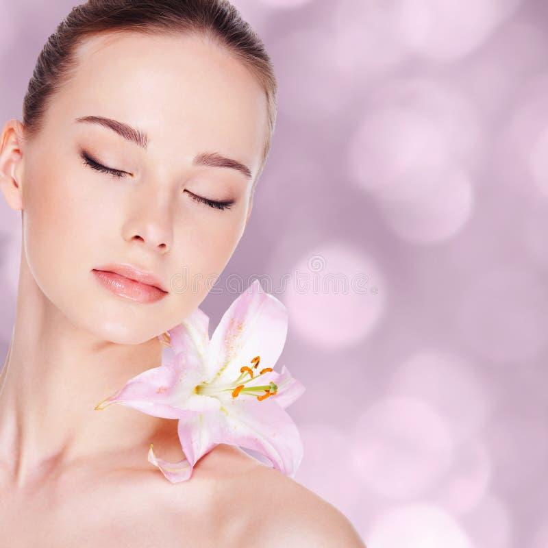 Mulher com pele e flor da saúde fotografia de stock