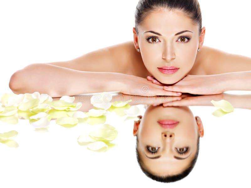 A mulher com pele saudável e rosa floresce reflexões em um mirro foto de stock royalty free