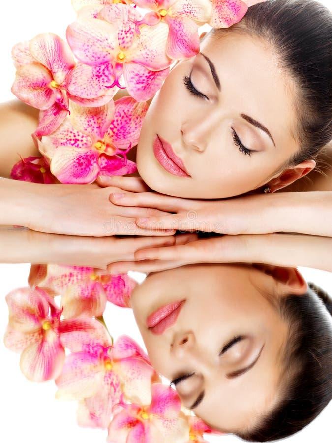 A mulher com pele saudável e rosa floresce reflexões em um mirro fotos de stock royalty free