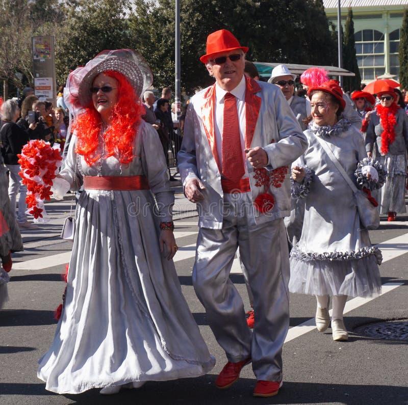 Mulher com peruca vermelha e homem com chapéu vermelho, par andando na parada de carnaval fotos de stock royalty free