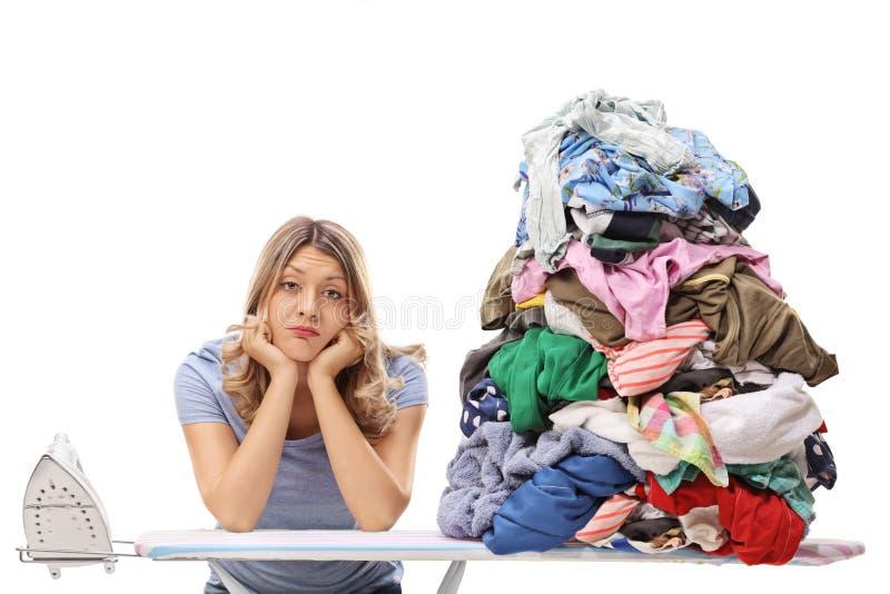Mulher com a pilha da roupa para passar fotografia de stock