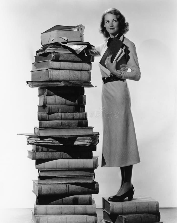 Mulher com a pilha de grandes livros (todas as pessoas descritas não são umas vivas mais longo e nenhuma propriedade existe Garan fotografia de stock royalty free