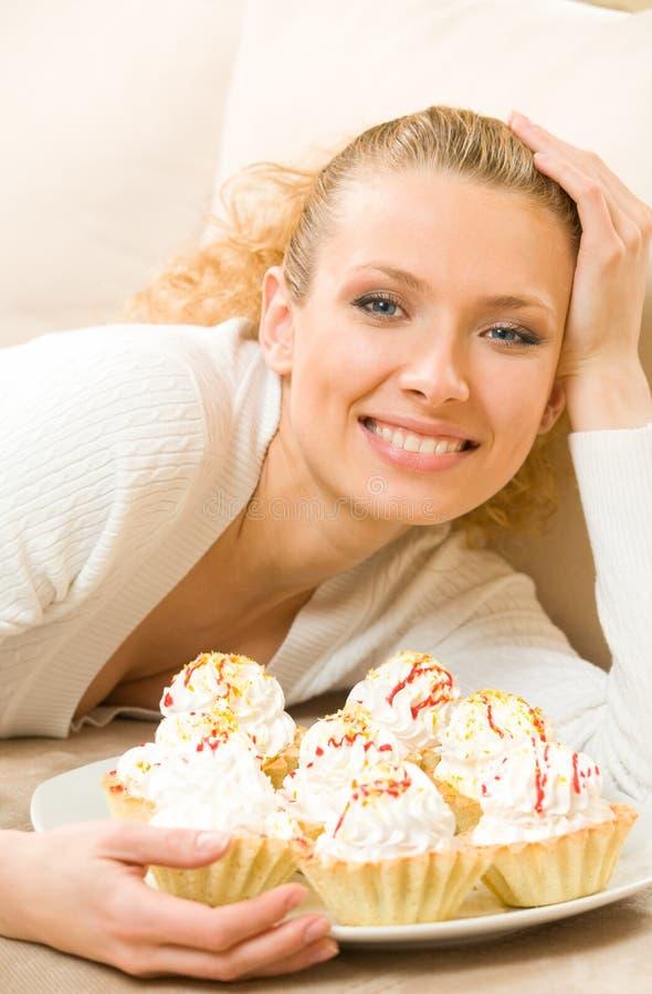 Mulher com a placa dos bolos fotografia de stock