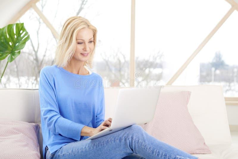 Mulher com portátil em casa imagens de stock royalty free