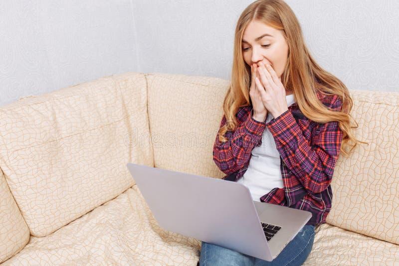 A mulher com portátil senta-se no sofá e nos olhares surpreendida foto de stock royalty free