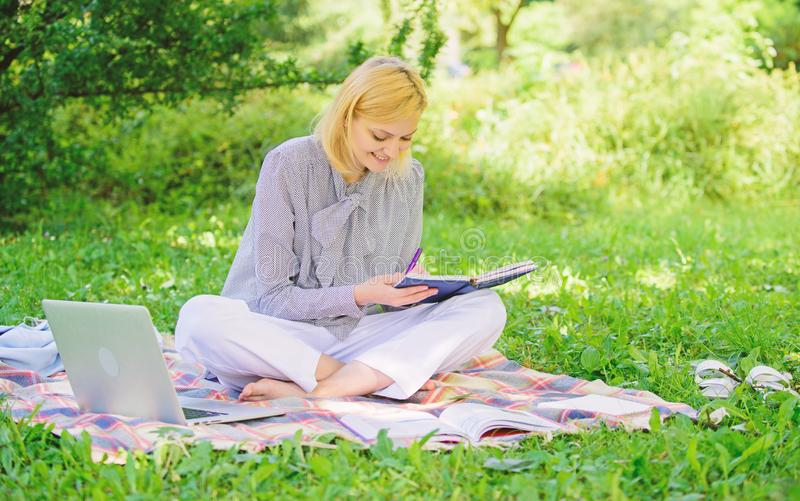 A mulher com port?til senta-se no prado da grama do tapete A menina com bloco de notas escreve a nota Conceito aut?nomo da carrei imagens de stock royalty free