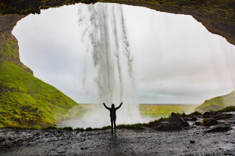 Mulher com posição levantada braços em Front Of Seljalandsfoss fotografia de stock