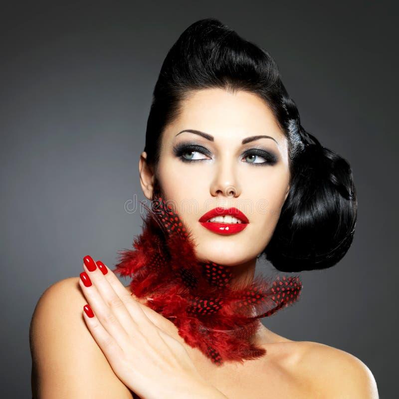 Mulher com pregos vermelhos e penteado criativo imagem de stock royalty free
