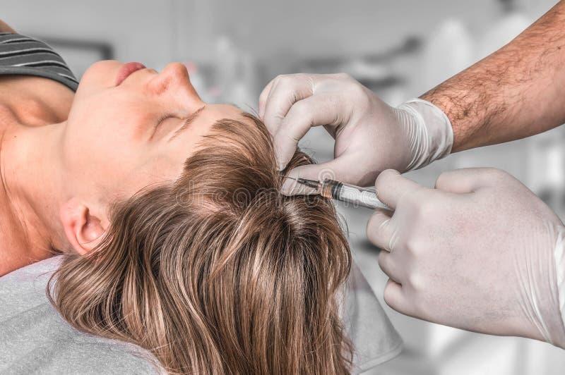 A mulher com problema do cabelo est? recebendo a inje??o imagem de stock