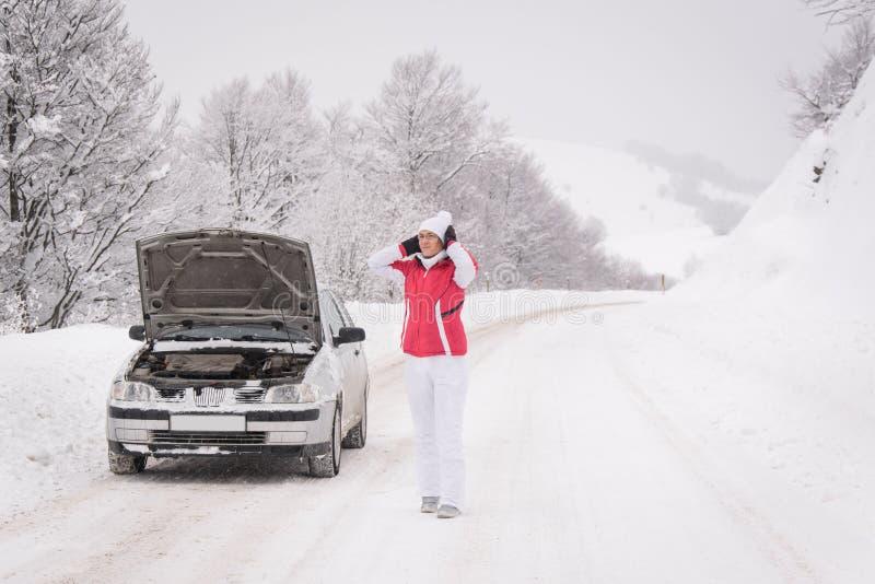 Mulher com problema do carro na estrada da montanha do inverno imagens de stock royalty free