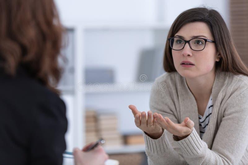 Mulher com problema e conselheiro durante a sessão de terapia fotografia de stock