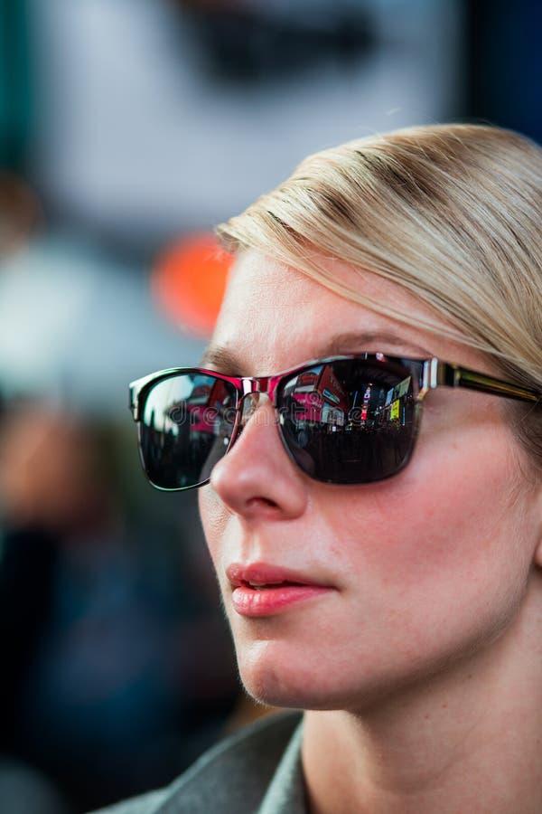 Mulher com reflexão das construções de Time Square nos óculos de sol em Nig foto de stock