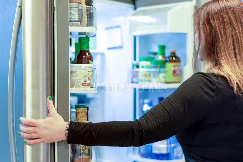 Mulher com refrigerador aberto fotografia de stock royalty free