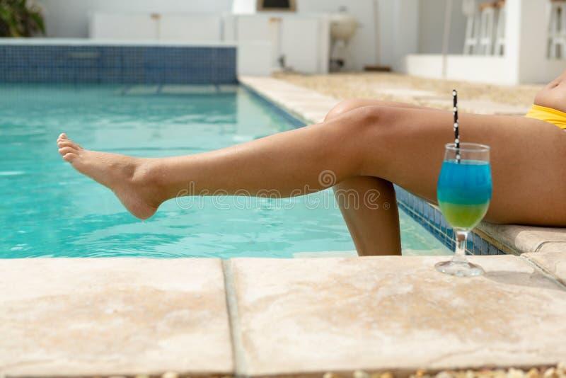 Mulher com relaxamento descalço na borda da piscina foto de stock