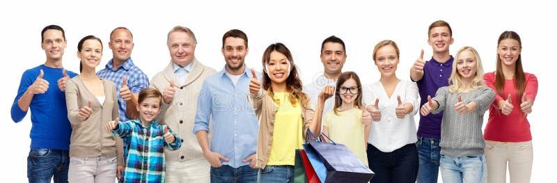 A mulher com sacos de compras e os povos mostram os polegares acima imagens de stock