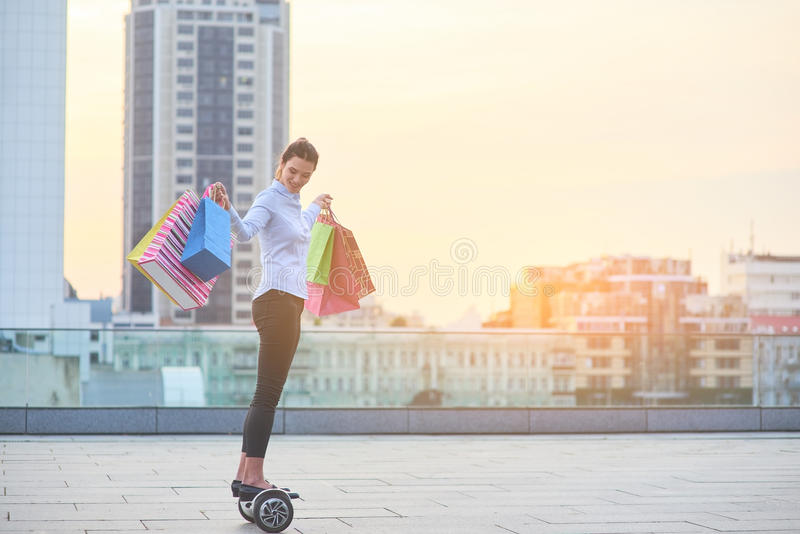 Mulher com sacos de compras, hoverboard imagem de stock
