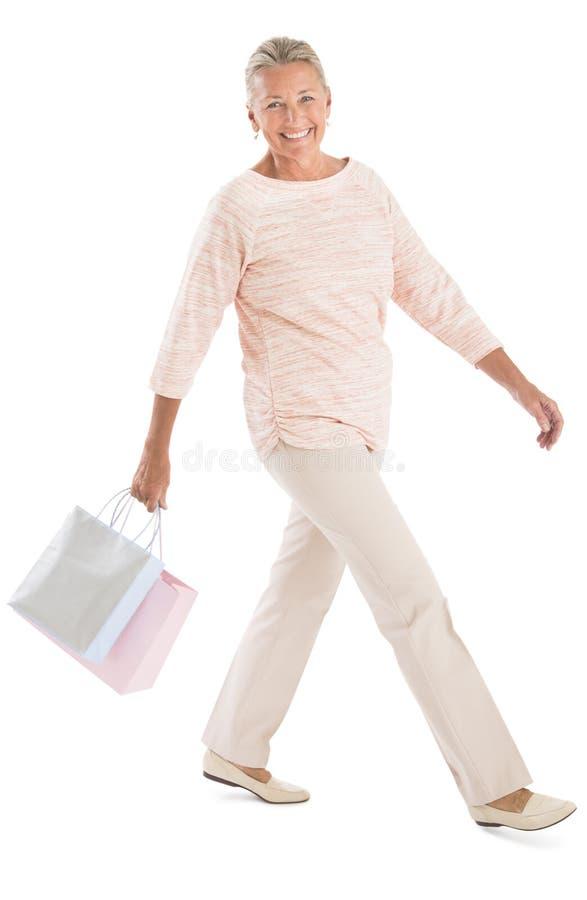 Mulher com sacos de compras que anda contra o fundo branco fotos de stock