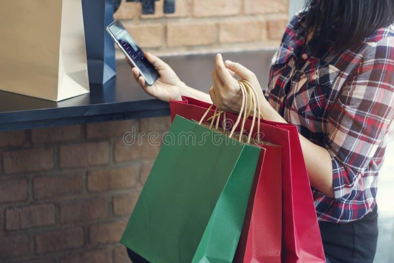 Mulher com sacos de compras usando o smartphone para o bankingn em linha foto de stock