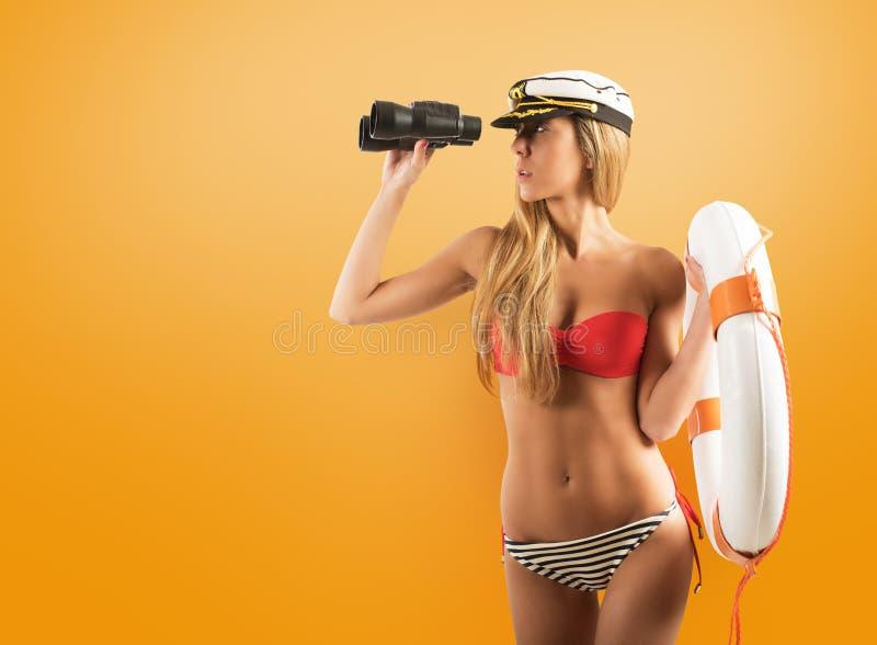 Mulher com a salva-vidas que olha para fora ao mar com bin?culos fotografia de stock